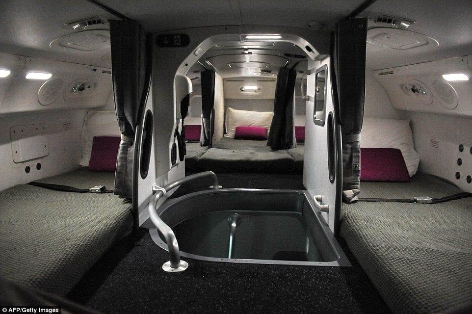 Inside the Hidden Bedrooms Where Cabin Crew Sleep: Flight Attendants Relax on Flat Beds Stowed Away in Plane Ceilings